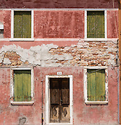 "Weathered red house with greenish yellow shutters. Burano, known for knitted lacework, fishing, and colorfully painted houses, is a small archipelago of four islands linked by bridges in the Venetian Lagoon, in the Veneto region of Italy, Europe. Burano's traditional house colors are strictly regulated by government. The Romans may have been first to settle Burano. Romantic Venice (Venezia), ""City of Canals,"" stretches across 100+ small islands in the marshy Venetian Lagoon along the Adriatic Sea in northeast Italy, between the mouths of the Po and Piave Rivers. Venice and the Venetian Lagoon are honored on UNESCO's World Heritage List."
