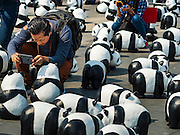 "04 MARCH 2016 - BANGKOK, THAILAND: A man takes pictures of the ""1600 Pandas+ World Tour in Thailand: For the World We Live In and the Ones We Love"" exhibit on Sanam Luang in Bangkok. The 1600 paper maché pandas, an art installation by French artist Paulo Grangeon will travel across Bangkok and parts of central Thailand for the next week and then will be displayed at Central Embassy, a Bangkok shopping mall, until April 10. The display of pandas in Thailand is benefitting World Wide Fund for Nature - Thailand and is sponsored by Central Embassy with assistance from the Tourism Authority of Thailand and Bangkok Metropolitan Administration and curated by AllRightsReserved Ltd.     PHOTO BY JACK KURTZ"
