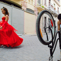 "A girl preparing to celebrate her quinceañera, or ""sweet 15"" birthday, passes by a boy fixing his bicycle in Old Havana."