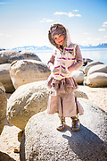 Stylish young girl in gold boots showing off rural, hippie kids fashion clothing at a Lake Tahoe Beach in Incline Village, Nevada.