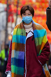 © Licensed to London News Pictures. 29/01/2020. London, UK. A woman is seen in London's Chinatown wearing a face mask following the outbreak of Coronavirus in Coronavirus in Wuhan, China which has killed 132 people and infected more than 6,000. According to the Department of Heath, 97 people have been tested for Coronavirus in the UK and all have been confirmed negative. Photo credit: Dinendra Haria/LNP