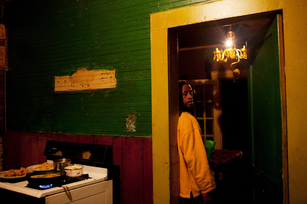 """Stone"" stands in the doorway of Ellen Wilson's kitchen after the wake for his nephew Demetrius ""Butta"" Anderson in the Baptist Town neighborhood of Greenwood, Mississippi on Thursday, November 4, 2010. A Vietnam Vet, Stone has been a crack addict for years and grinds his teeth incessantly."