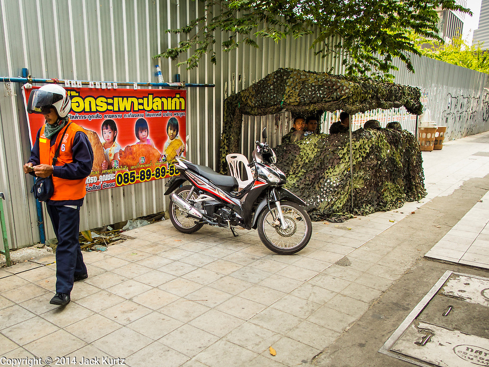 29 JANUARY 2014 - BANGKOK, THAILAND: A Thai motorcycle taxi in front of a Thai army position of Phaya Thai Road. The Thai army has deployed small numbers of soldiers as anti-government protests gain traction. The army is widely thought to be sympathetic to the protestors. Thais are supposed to vote Sunday, February 2 in a controversial national election. Anti-government protestors have vowed to disrupt the election. One person was killed and several injured in election related violence during early voting on Sunday Jan. 25. The ruling Pheu Thai party is widely expected to win the election, which is being boycotted by the Democrats and opposition parties.      PHOTO BY JACK KURTZ