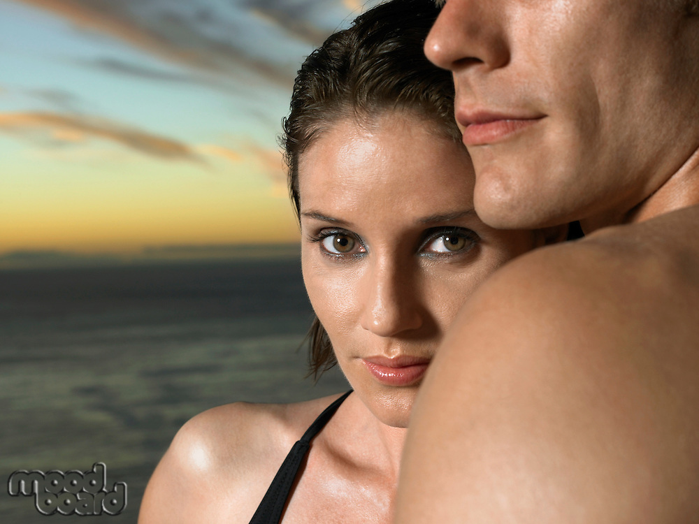Woman next to man at sunset near ocean