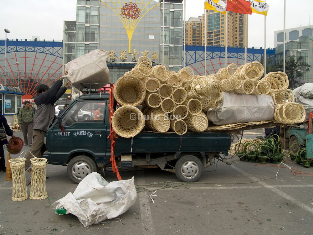 a traveling sales person packing his car at a open door woven basket market in Beijing China