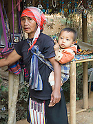Akha hill tribe woman carrying grandson in carrier on back; Mae Salong; Thaiiland