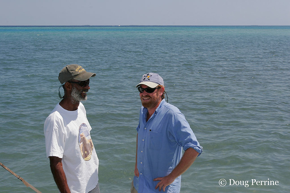 guide Eloy Cuevas (left) and Dr. Will Heyman (right) share a story on their way out to collect fish landings data in the Gladden Spit & Silk Cayes Marine Reserve, off Placencia, Belize, Central America ( Caribbean Sea )