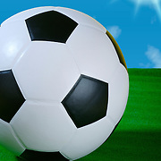 Studio shot of a black and white soccer ball shot from a low angle with green turf and sun and a blue sky with clouds.