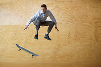 Man crouching jumping from skateboard mid-air in front of interior wall