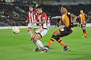 Hull City striker Chuba Akpom (19) crosses ball against Nico Yennaris (28) of Brentford during the Sky Bet Championship match between Hull City and Brentford at the KC Stadium, Kingston upon Hull, England on 26 April 2016. Photo by Ian Lyall.