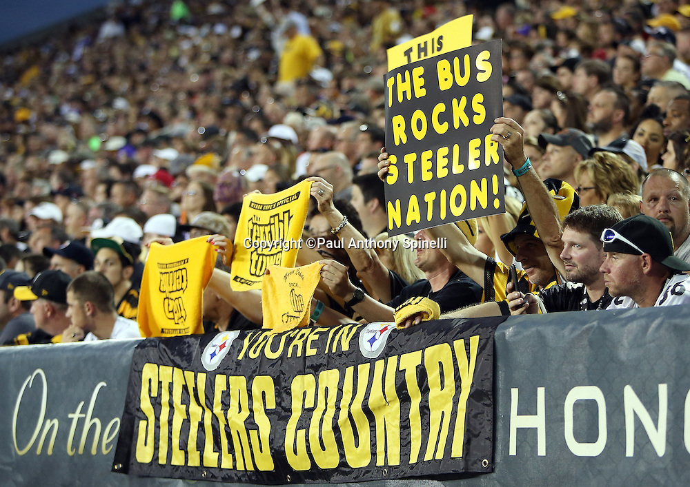 Pittsburgh Steelers fans hold up signs including one referencing The Bus during the 2015 NFL Pro Football Hall of Fame preseason football game against the Minnesota Vikings on Sunday, Aug. 9, 2015 in Canton, Ohio. The Vikings won the game 14-3. (©Paul Anthony Spinelli)