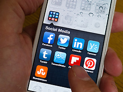detail of iPhone 5 screen with many social media app icons