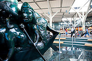 "YVR, Vancouver, B.C. International Airport.  The interior design of the International Terminal was inspired by British Columbia's great outdoors and the art of the Northwest Coast that depicts British Columbia's native wildlife, mountains, rivers, forests, and aboriginal heritage. .The Spirit of Haida Gwaii, The Jade Canoe, by Bill Reid, provides the focal point to the entrance of the International Terminal. The bronze sculpture features legendary Haida creatures paddling a boat that ""goes on, forever anchored in the same place."""