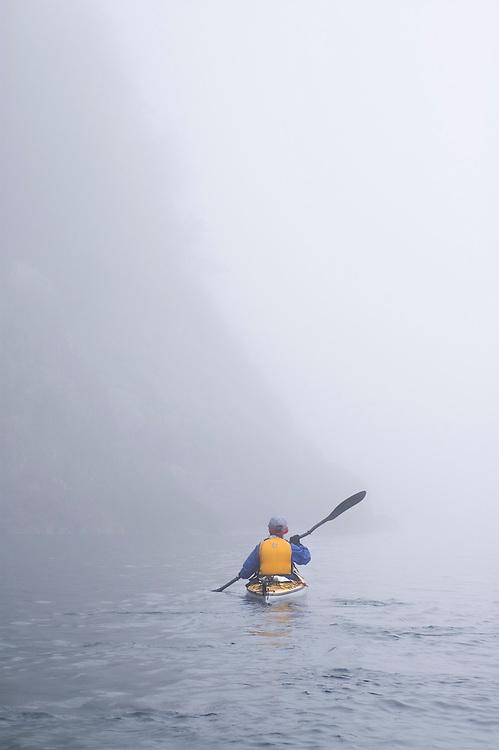 A sea kayaker paddles through the fog in Lake Superior Provincial Park near Wawa Ontario Canada.