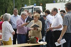 """Der Leiter des Museums """"Altes Zollhaus"""" in Hitzacker, Klaus Lehmann (Mitte), beim Besuch von Bundeskanzlerin Angela Merkel (CDU) anlässlich des Jahrhunderthochwassers der Elbe im Juni 2013<br /> <br /> Ort: Hitzacker<br /> Copyright: Karin Behr<br /> Quelle: PubliXviewinG"""