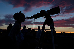 Ella peers through a telescope at the star party, held the night before crowds come to watch the total solar eclipse in Madras, Oregon on Sunday, August 20, 2017. The eclipse will be sweeping across a narrow portion of the contiguous United States from Lincoln Beach, Oregon to Charleston, South Carolina on August 21. A partial solar eclipse will be visible across the entire North American continent along with parts of South America, Africa, and Europe.  Photo Credit: (NASA/Aubrey Gemignani)