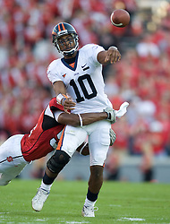 Virginia quarterback Jameel Sewell (10) throws the ball has he is hit by a NCSU defender.  The North Carolina State Wolfpack defeated the #15 Virginia Cavaliers 29-24 at Carter Finley Stadium in Raleigh, NC on October 27, 2007.