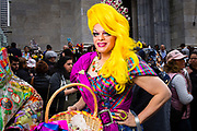 New York, NY - 21 April 2019. A man with long, bright yellow hair, wearing a dress and carrying an Easter basket fillwd with lollipops at the Easter Bonnet Parade and Festival on New York's Fifth Avenue.