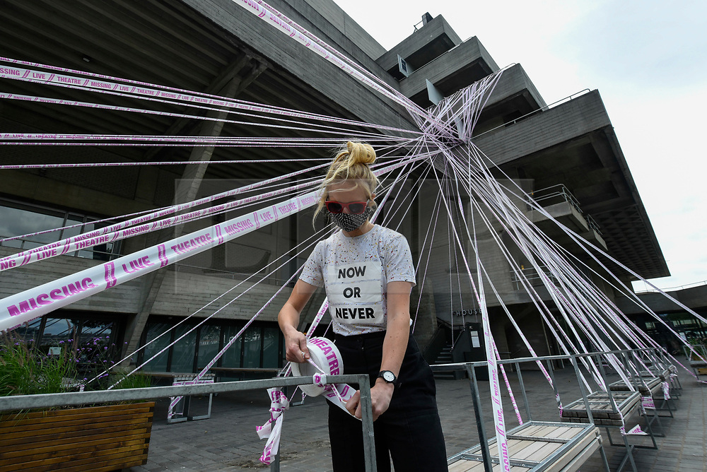 © Licensed to London News Pictures. 03/07/2020. LONDON, UK.  A staff member checks pink tape wrapped around the National Theatre on the South Bank as part of the #MissingLiveTheatre initiative, a project by theatre designers Scene Change to support those in the live theatre industry through Covid-19 and to help theatres bring shows back into production.  So far, 50 theatres across the UK have signed up to the initiative.  Theatres are remain closed even though the UK government has relaxed certain coronavirus pandemic lockdown restrictions allowing other businesses to reopen.  Photo credit: Stephen Chung/LNP