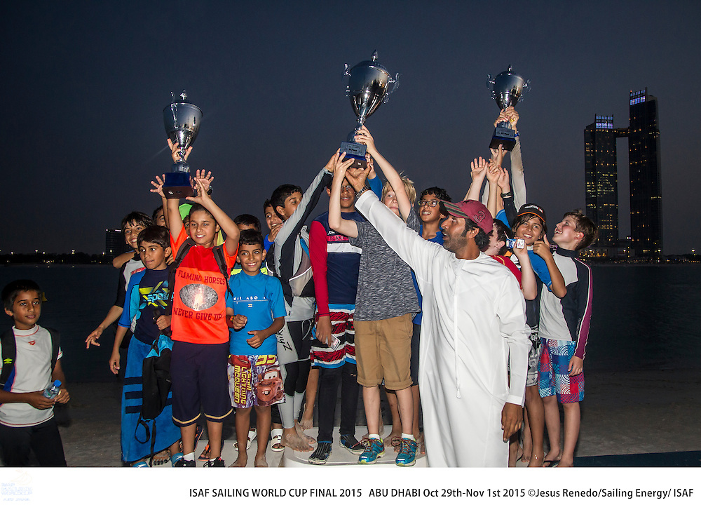 Local sailing school and olympic sailors together sailing optimist. 2015 ISAF Sailing World Cup Final, Abu Dhabi, United Arab Emirate. Eight Olympic sailing events are being contested along with open kiteboarding from 29th October to November 1st, 2015. Prize money will be awarded to the top three overall finishers in each of the events for a total prize purse of US$220,000. The Abu Dhabi Sailing and Yacht Club is the host of the ISAF Sailing World Cup Final, located on the main island of the city with immediate access to the beautiful waters of the Arabian Gulf.  Race areas are placed around Lulu Island off the UAE capital&rsquo;s stunning Corniche.<br /> <br /> Credit Jesus Renedo/Sailing Energy/ Isaf