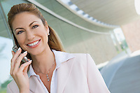 Businesswoman using cell phone on balcony, portrait