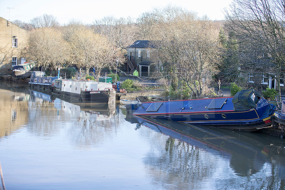 © Licensed to London News Pictures. 29/12/2015. Elland UK. Picture shows narrow boats left stranded on the banks of the Calder & Hebble Navigation at Greenway in Elland after recent flooding.  Photo credit: Andrew McCaren/LNP