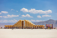 The Temple of Direction by: Geordie Van Der Bosch from: San Francisco, CA year: 2019 The Temple of Direction is organized linearly. It recreates a restricted passage which expands in the center into a large hall. This is a response to the openness of the playa; it creates a space traveled end to end; versus wandering an open plan; this temple provides direction and focus. Linearity also reflects the passage of life; all lives have a beginning, a middle and an end which metaphorically is included in this temple's form. Following this metaphor a variety of spaces are created; narrow spaces and wide spaces, dark spaces and bright spaces. Tunnels create intimate experiences with shade.. A large central hall expands in width and height providing a bright area suitable for gatherings. URL: https://www.templeofdirection.org Contact: templeofdirection@gmail.com https://burningman.org/event/brc/2019-art-installations/?yyyy=&artType=H#a2I0V00000167U9UAI