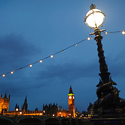 An ornate street light with a string of lights comign from it in the foreground, with Big Ben and the Houses of Parliament (Palace of Westminster) in the background. Taken at dusk.