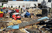 Dave Andrews sits among debris in his friend's yard in the aftermath of Hurricane Irene in East Haven, Conn.(AP Photo/Jessica Hill)