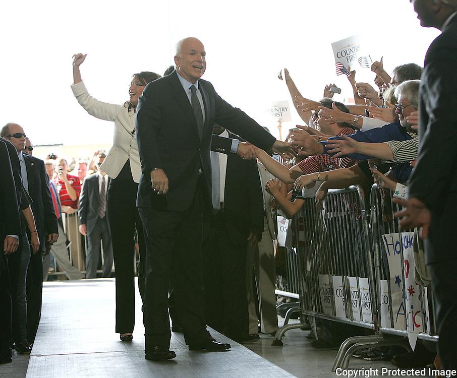 US Republican presidential nominee Senator John McCain (R-AZ)  and his running mate Alaska Govenor Sarah Palin enters the hanger for a campaign rally in Cedar Rapids, Iowa, September 18, 2008.