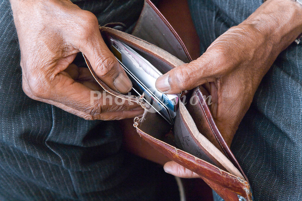 Older man counting money in his wallet,