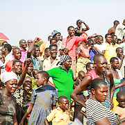 CAPTION: Onlookers on the shore of Lake Kyoga, at different levels of excitement and anxiety, as they support their favorites in the Kaberamaido Boat Race. LOCATION: Lake Kyoga, Abrepoli, Kaberamaido District, Uganda. INDIVIDUAL(S) PHOTOGRAPHED: Multiple people.