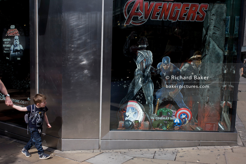 A young boy pulls his father towards The Avengers characters in the Disney shop, London.