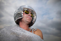 "© Licensed to London News Pictures . 24/08/2012 . Leeds , UK . Paul Burman (aka "" Disco Balls "") from Newcastle soaks up the sun outside his camper van at the Leeds Festival in Bramham Park . Photo credit : Joel Goodman/LNP"