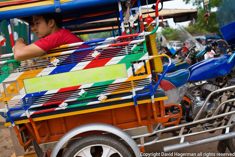 A tuk tuk driver awaits a fare in the busy Lao capital.