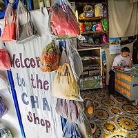 Cambodia has been dealing with the insurmountable task leftover from decades of war and its legacy, unexploded ordnance or UXOs. Estimates range from 3 to 9 million unexploded bombs that are still just beneath the surface throughout the region. These bombs are left over from air strikes, artillery fire, mortar shells, rockets, grenades, anti-personnel and anti-vehicle land mines are indiscriminate weapons and do not expire, often killing or injuring between 100 to 200 people in Cambodia a year. With little resource, the countries' people and Non Governmental Organizations (NGOs) are still facing over a hundred years being exposed to this deadly issue while walking and cultivating their land in fear.<br /> <br /> Cambodian Handicraft Association (CHA) Director, Hay Kim Tha amongst the shelves of hand made clothes, toys and bags at The office in Phnom Penh, Cambodia. CHA helps land mine and polio disabled by teaching crafts to help support themselves. Jan. 2013.