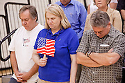 "Aug 10, 2009 -- CHANDLER, AZ: People opposed to health care reform bow their heads in prayer before a town hall meeting on health care reform in Chandler, AZ. Rep. Jeff Flake, (R-AZ) hosted a ""town hall"" style meeting on health care reform at Basha High School in Chandler Monday. Flake, a conservative Republican, has opposed President Obama on many issues, like the stimulus and health care reform. Protestors who have shut down similar meetings hosted by Democrats, gave Flake a warm welome. About 1,600 people attended the meeting.   Photo by Jack Kurtz"
