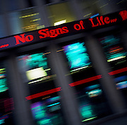 During a journey into America's hinterlands, days after the September 11th attacks in New York and Washington DC, the breaking news flashes from Fox TV's studios that there are expected to be no more survivors found at Ground Zero. The tragic message reads 'No Signs of Life' in large red letters, read by passers-by along the on the Avenue of the Americas on Manhattan. As the news travels across the building, the camera blurs other TV pictures of live broadcasts with a sense of urgency, speed and desperation in the fruitless search for life.