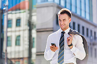 Portrait of mature businessman using smartphone while walking on pavement after work