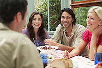 Group of young people sitting at verandah table laughing