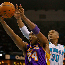 Mar 29, 2010; New Orleans, LA, USA; Los Angeles Lakers guard Kobe Bryant (24) shoots past New Orleans Hornets forward David West (30) during the second half at the New Orleans Arena. The Hornets defeated the Lakers 108-100. Mandatory Credit: Derick E. Hingle-US PRESSWIRE