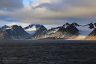Glaciers flow down mountain valleys to the sea in Smeerenburgfjorden along northern coast of Spitsbergen island; Svalbard, Norway.