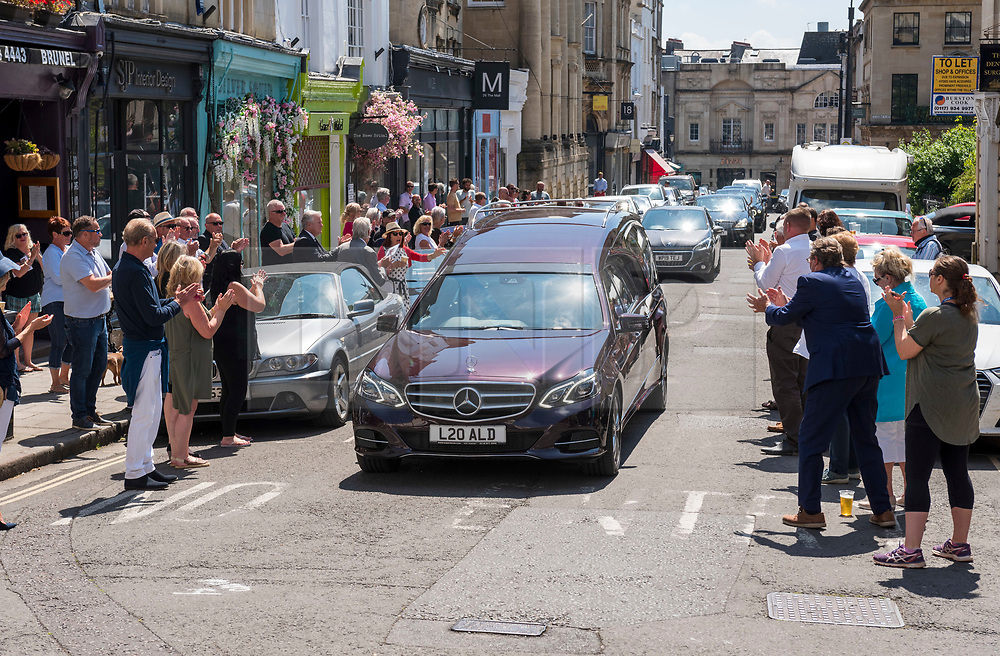 © Licensed to London News Pictures;21/05/2020; Bristol, UK. People applaud the funeral cortege procession for former restauranteur Barry Yuille with a hearse and family travelling in vehicles through the Clifton Village area of Bristol. Described as a larger than life character in the area, normally hundreds of mourners would have been expected to attend his funeral, but attendance at funerals is still restricted to 10 of close family and friends to prevent the spread of the Covid-19 virus under the coronavirus lockdown. Though the Government has eased some restrictions, people are still asked to maintain social distance to prevent the spread of the Covid-19 virus. Barry Yuille, a former restaurateur, has died aged 69 following cancer. He had been an interpreter for BAE working on the Concorde project in Toulouse, and then ran restaurants in Spain and Bristol. In the 1980s, he opened up a restaurant called Bon Viveur in Bristol and it became the place to go for celebrities at the time including stars from entertainment and sports. It's reported that he was great friends with well known Bristol restaurateur Keith Floyd, and was Keith's best man twice. Barry leaves a son and daughter, Oliver and Vanessa, grandchildren, and his devoted partner Gillian, who cared for him to the end of his life. Photo credit: Simon Chapman/LNP.