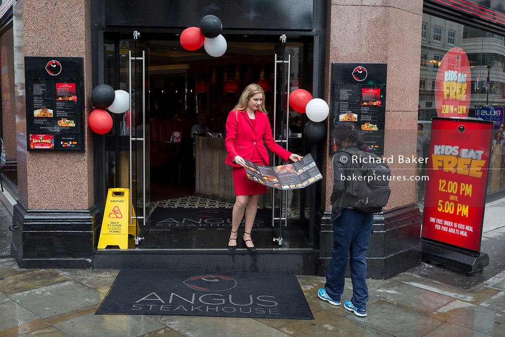 A member of staff with Angus Steakhouse shows their menu to passers-by on Coventry Street, on 13th August 2018, in London, England. Angus Steakhouse is the original chain of steak restaurants based in central London's West End and has been serving both Londoners and visitors alike for 50 years.