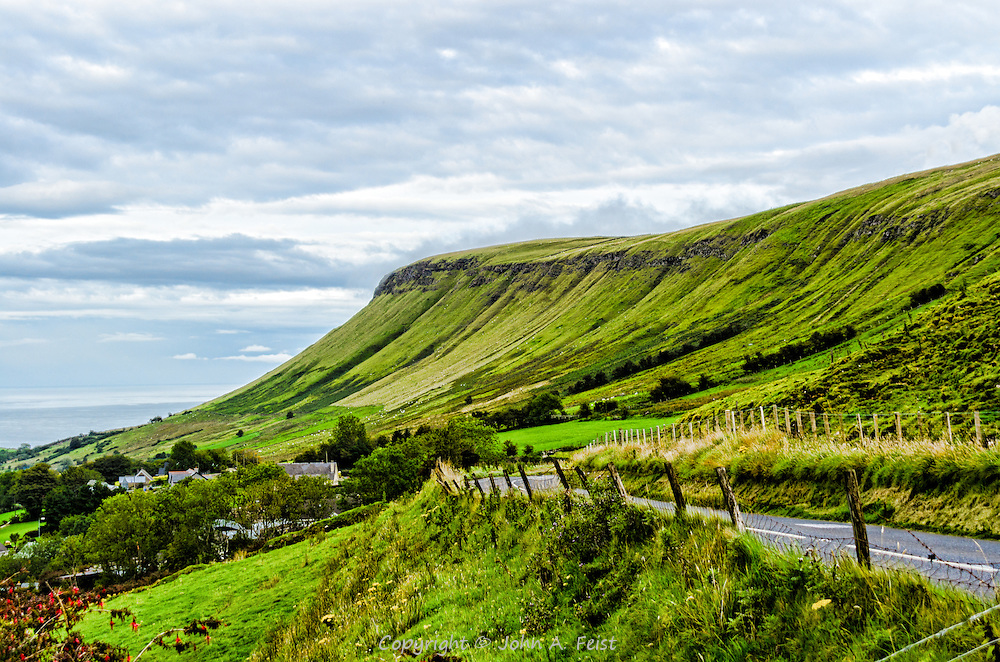 Descending almost to the sea approaching Cushendall, county Antrim, Northern Ireland.  The cliffs are covered in Ireland's emerald green and seem to just drop off into the sea.  This is a beautiful area, mostly rural with plenty of sheep grazing