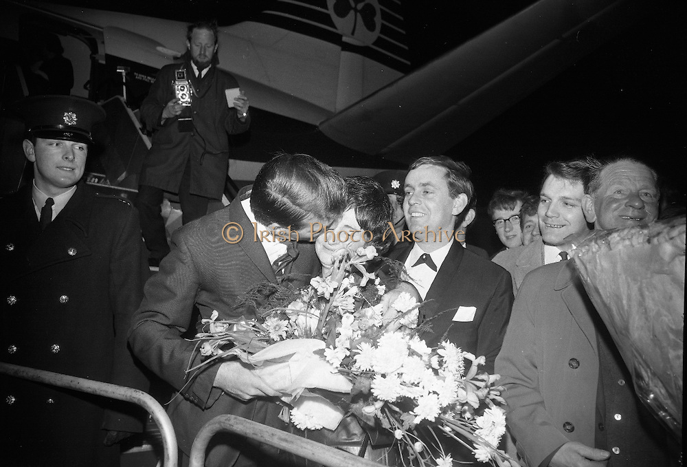 """Seán Dunphy returns to Dublin Airport from Vienna after taking second place in the Eurovision Song Contest with the song """"If I Could Choose"""".  Dunphy greets his wife as he steps from the plane to a hero's welcome from thouands of fans crowding the balconies of Dublin Airport..10.04.1967"""
