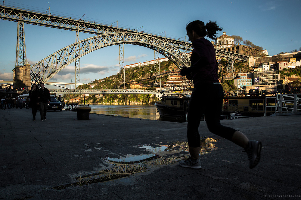Woman running in Porto ribeira by the Douro river. Portugal