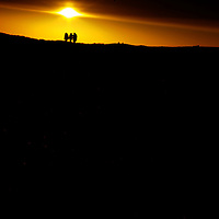 Winter sunset with three figures on the horizon at Walberswick, Suffolk, England