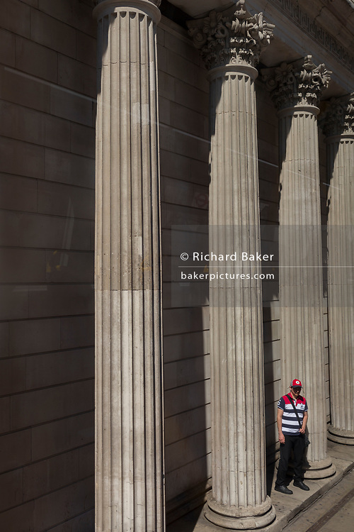 A man waits for a bus beneath the pillars and columns of the Bank of England on Threadneedle Street in the City of London, the capital's financial district aka the Square Mile, on 15th May 2018, in London, UK.