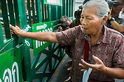 "01 FEBRUARY 2014 - BANGKOK, THAILAND: A Thai voter tries to get through a locked gate at the Din Daeng polling place in Bangkok. Thais went to the polls in a ""snap election"" Sunday called in December after Prime Minister Yingluck Shinawatra dissolved the parliament in the face of large anti-government protests in Bangkok. The anti-government opposition, led by the People's Democratic Reform Committee (PDRC), called for a boycott of the election and threatened to disrupt voting. Many polling places in Bangkok were closed by protestors who blocked access to the polls or distribution of ballots. The result of the election are likely to be contested in the Thai Constitutional Court and may be invalidated because there won't be quorum in the Thai parliament.    PHOTO BY JACK KURTZ"